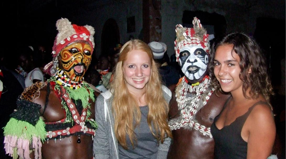 Projects Abroad volunteers at a night time event experiencing Senegalese culture with men in traditional clothing